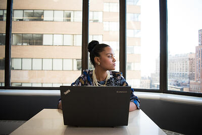 woman-sits-in-front-of-black-laptop